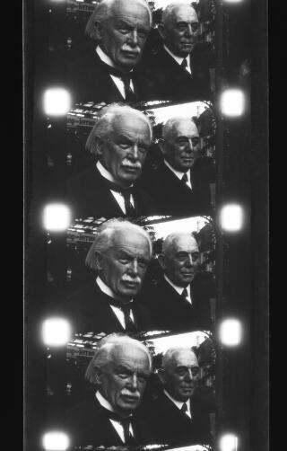 Pedwar ffrâm o ffilm cine yn dangos David Lloyd George gyda dyn canol oed anhysbys.