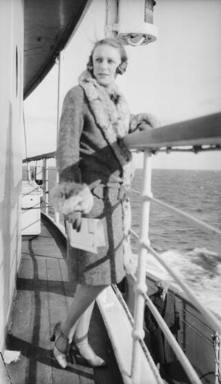 A well-dressd young woman leaning against a handrail on an upper deck of a ship. Identity of sitter not known.