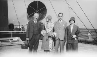 From left to right, a middle aged gent wearing spectales, young lady in fur trimmed coat, A J Sylvester, lady in two piece suit. Both women are wearing cloche hats.