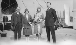 L-R A bespectacled middle aged gent, lady in two piece suit, young lady in fur trimmed coat, gent in dark suit photographed on the deck of a ship.