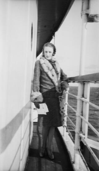 Young lady in fur-trimmed coat aboard a ship.