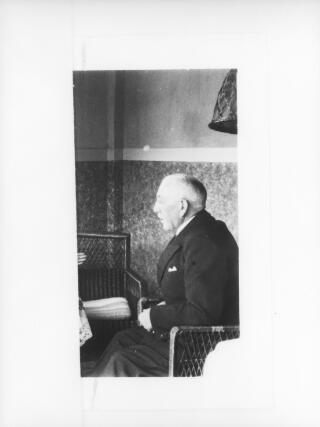 Copy photograph of an elderly man sitting in a wicker chair and photographed in profile. Identity of sitter unknown.