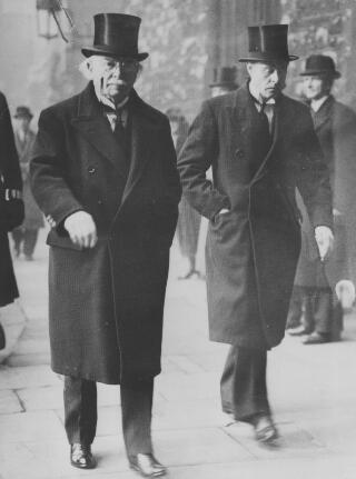 Copy of a photograph of AJS and D Ll G walking along a city street, both looking serious.