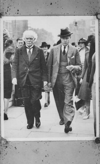Copy of a photograph of D LlG and AJS walking along a city street. AJS is wearing a hat.
