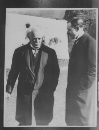 Copy photograph of David Lloyd George talking to a young A J Sylvester. They appear to be in a garden.
