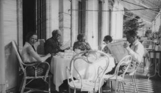 Cymdeithion Lloyd George yn eistedd o amgylch bwrdd ar deras gwesty. Mae Gwilym yn darllen 'Journal de Geneve'. Ceir yr argraff fod pawb newydd orffen eu brecwast.