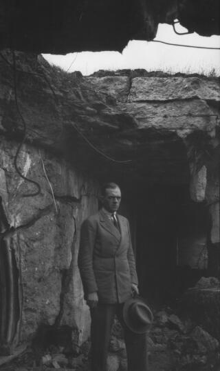 Gwilym Lloyd George wrth fynedfa caer danddaearol wedi ei naddu o'r graig.